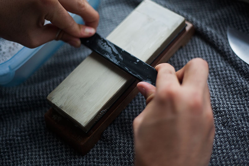 using a whetstone to sharpen the edge of a knife